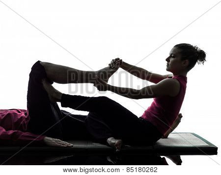 one man and woman performing feet legs thai massage in silhouette studio on white background