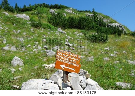 red sign on path of Durmitor National Park, Zabljak NOTE: in the sign there are proper names of mountain and cave in montenegrin language http://www.shutterstock.com/blog/images-with-non-english-text