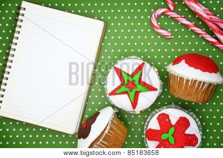 Festive Christmas cupcakes and blank cookbook page on green background