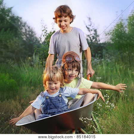three friends playing in the plane using a garden carts (focus only on child in cart)