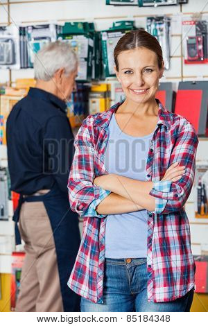 Portrait of confident female customer with arms crossed standing against worker in hardware store