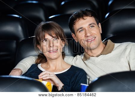 Smiling mid adult couple watching movie in cinema theater