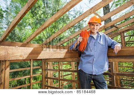 Portrait of confident male worker holding pipe in incomplete wooden cabin at construction site