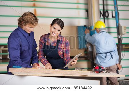 Portrait of female carpenter holding digital tablet while standing by colleague in workshop