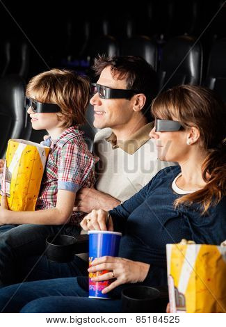 Family of three having snacks while watching 3D movie in cinema theater