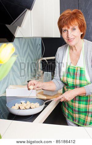 Female cooking at kitchen. Woman preparing pasta