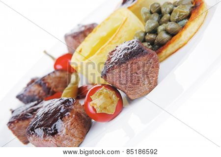 european food: grilled beef meat on white china plate isolated on white background hot pepper, capers and sauces