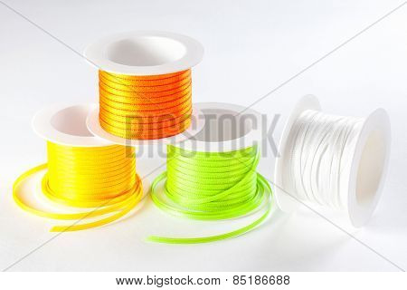 four spools of ribbon on white background