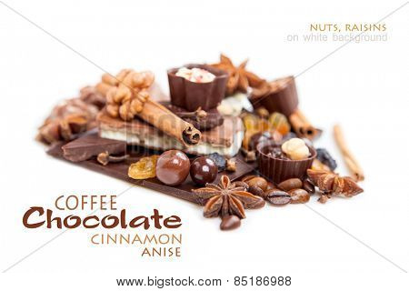 Various pieces of chocolate with nuts, raisins and coffee beans on a white background