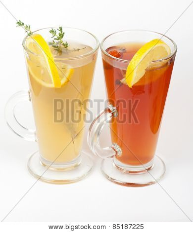 Two tea glasses with thyme lemon and briar on a white