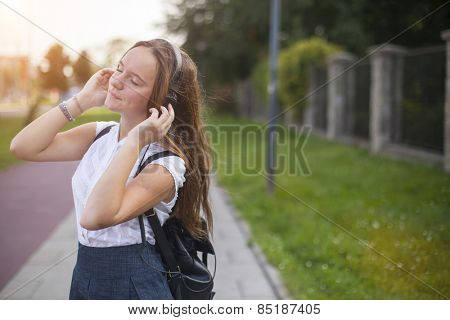 Young cute girl enjoying music with headphones outdoors in the mild sunshine.