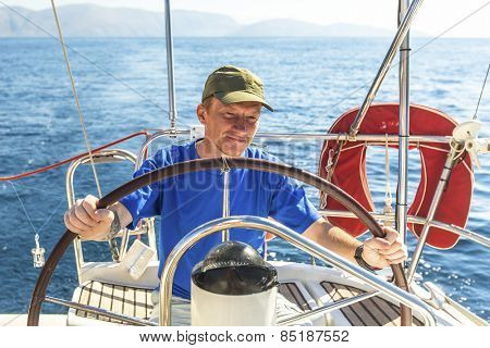 Young man skipper at the helm controls sailing yacht.
