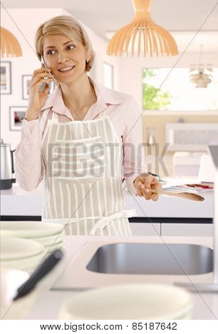 Blonde casual caucasian housewife in bright kitchen with mobile phone, indoors, standing, wooden spoon in hand, cooking, wearing apron.