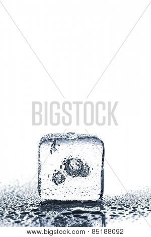 Melting ice cube with air bubble inside on white background with copy space