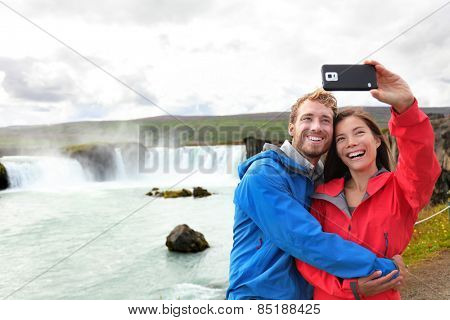 Selfie couple taking smartphone picture of waterfall Godafoss outdoors on Iceland. Couple visiting famous tourist attractions and landmarks in Icelandic nature landscape. Mixed race couple having fun.