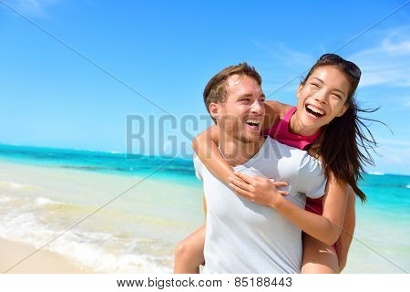 Happy couple in affection on shoreline summer excursions. Upbeat Asian young lady piggybacking on yo