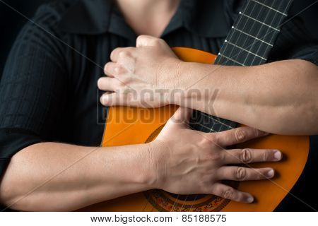 Classic guitar closeup - Musician hands embracing a classic acoustic guitar