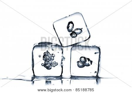 Three melting ice cubes with air bubbles inside on white background