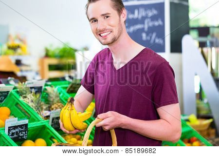 Man selecting bananas while grocery shopping in organic supermarket