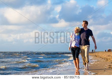 Couple take a romantic walk through sand and waves at German north sea beach