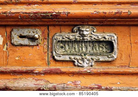 Old mailbox slot in an old wooden door painted orange