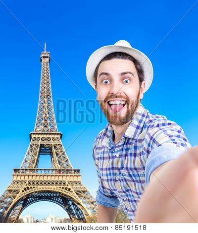 Happy young man taking a selfie photo in Paris, France