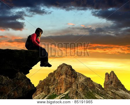 Girl sitting on a rock in the Sexten Dolomites , Italy