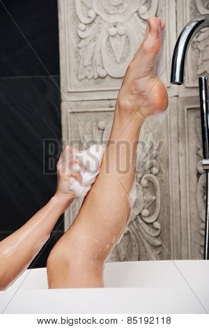 Beautiful bathing woman cleaning her leg with sponge.