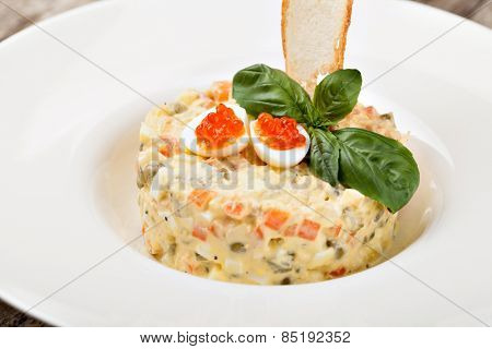 Salade Olivier decorated with red caviar, mayonnaise