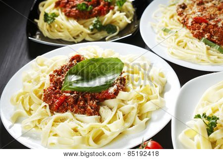 Spaghetti bolognese in plates on black table