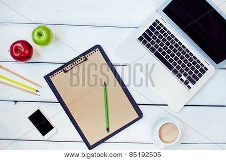 Table with laptop, clipboard with paper, phone, pencils, apples, and coffee