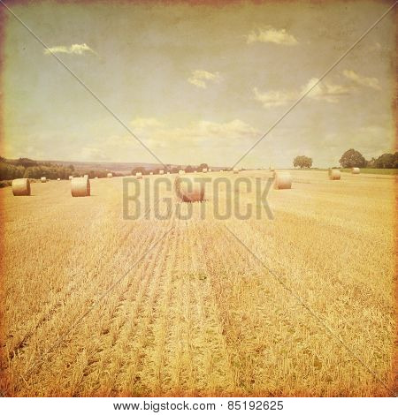Agricultural field with hay bales in grunge and retro style.