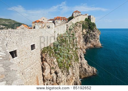 DUBROVNIK, CROATIA - MAY 26, 2014: Old city walls build on cliffs and houses inside the walls. City wall is one of most popular tourist attraction in Dubrovnik.