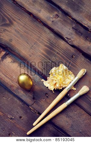 Paintbrush and gold leaf with painter egg
