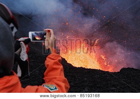 Eruption Tolbachik Volcano on Kamchatka, girl photographed lava lake in crater in mobile phone