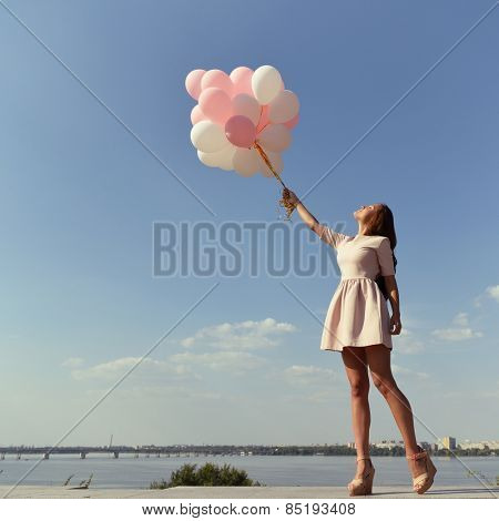 Fashion girl with  air balloons over blue sky, toned