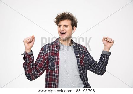 Young man listening the music in headphones and dancing