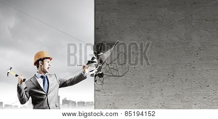 Young businessman in suit and hardhat hammering nail in wall