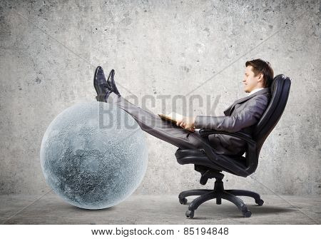 Young businessman sitting in chair with book in hands