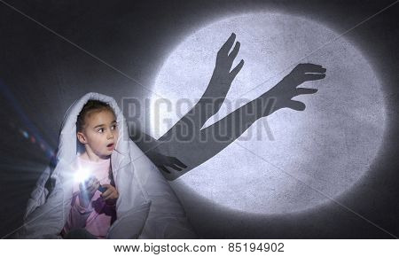 Cute girl in bed under blanket with flash light