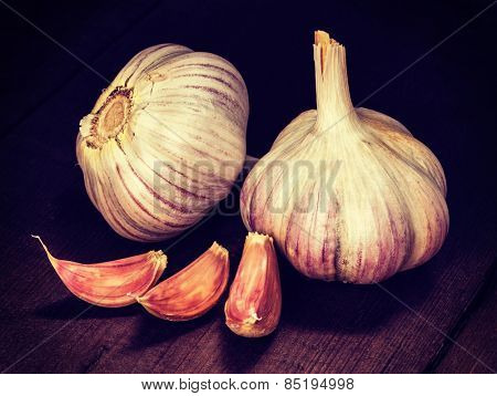 Vintage retro effect filtered hipster style image of garlic and cloves on old wooden background