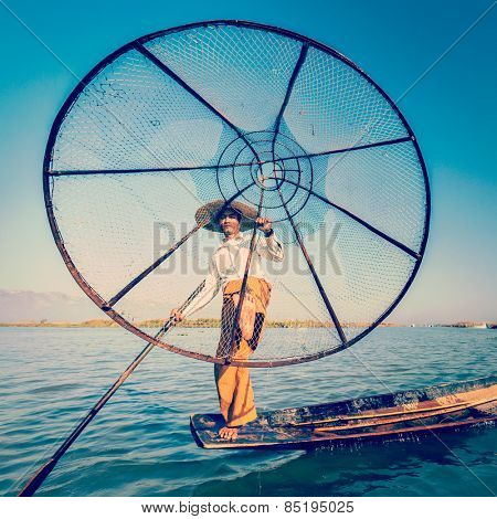 Vintage retro effect filtered hipster style image of Myanmar traditional Burmese fisherman with fishing net at Inle lake in Myanmar famous for their distinctive one legged rowing style