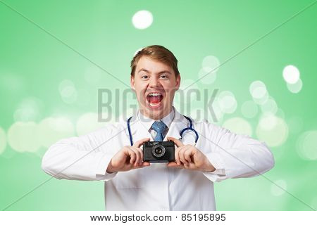 Funny young doctor with photo camera screaming emotionally