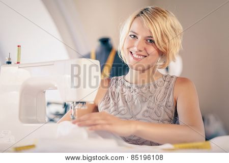 Young woman dressmaker working on sewing machine