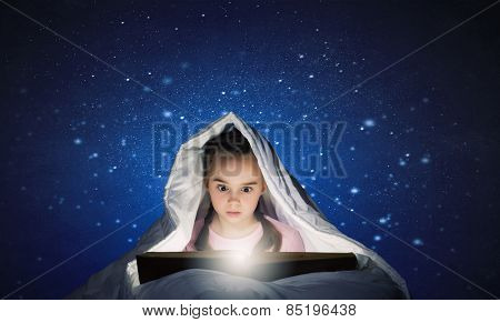 Cute girl in bed under blanket with book in hands