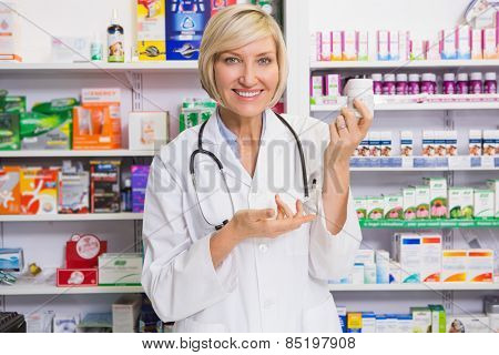 Smiling pharmacist showing medication at camera in the pharmacy