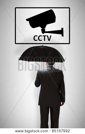 Mature businessman holding an umbrella against cctv