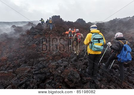 Group Of Tourists Hiking On Lava Field Eruption Tolbachik Volcano On Kamchatka Peninsula. Russia