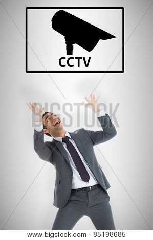 Scared businessman with arms raised against cctv