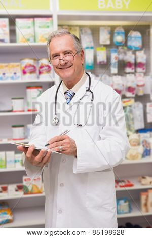 Smiling senior doctor writing on clipboard in the pharmacy